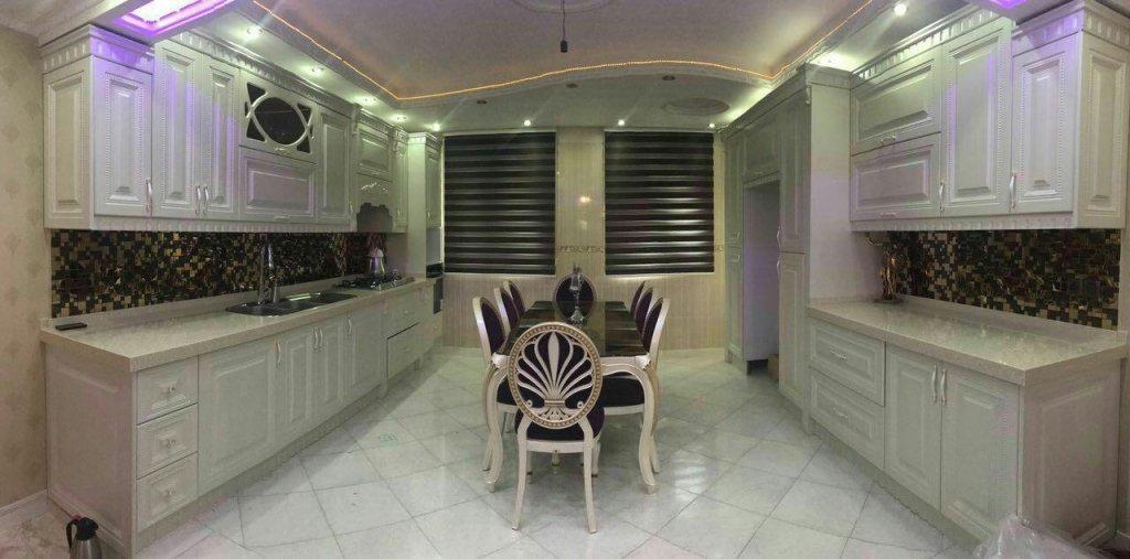 کابینت ممبران کرم با طرح بدون جزیره و میز بسیار زیبا در وسط فضای آشپزخانه